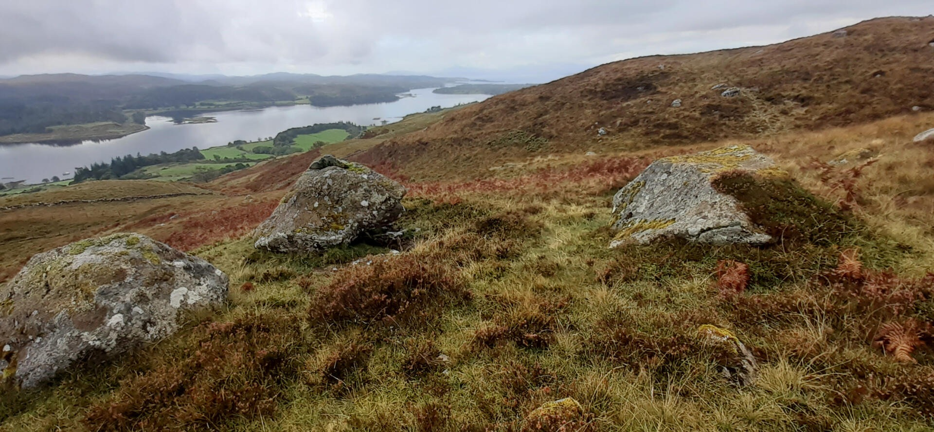 Open hillside with boulders in the foreground and a loch in the background